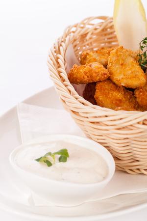 nuggets pollo: Crispy fried empanadas nuggets de pollo en una canasta de mimbre servida como un dedo o un aperitivo con un dip cremoso en un bol junto con Foto de archivo
