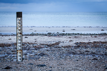 spring tide: Tidal marker with a measurement scale to measure the depth of the incoming high tide implanted on a coastal beach to record flooding and natural disasters Stock Photo