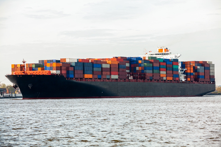 laden: Fully laden container ship in port with its decks stacked with metal containers full of freight and cargo for international destinations