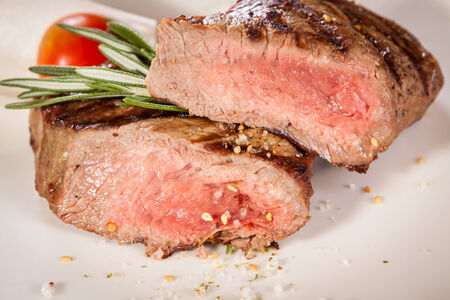 medium close up: Succulent medium rare beef steak sliced through to display the tender red flesh and seasoned with spices and fresh rosemary, close up view