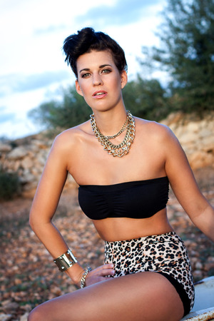 Glamorous beautiful young woman in animal print shorts and stylish elegant jewellery posing sitting outdoors looking at the camera photo