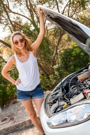 annoyance: Attractive young blond woman inspecting her car engine after a breakdown at the roadside frowning in annoyance and frustration