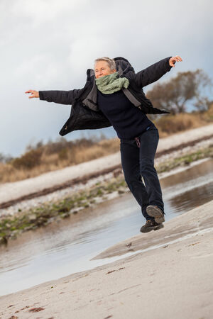 frolicking: Happy senior woman frolicking on the beach striding along with outspread arms and a smile of appreciation as she enjoys nature and the freedom of her retirement