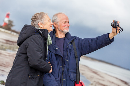 Elderly couple taking a self portrait on a compact digital camera posing in the open air and sunshine with their heads close together smiling at the lens photo
