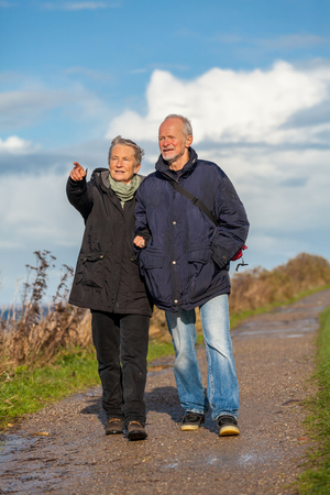happy elderly senior couple walking on beach healthcare recreation photo