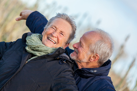 Attractive elderly couple in warm clothing standing clue together with outstretched arms, closed eyes and laughing smile against a blue sky embracing and celebrating the sun photo