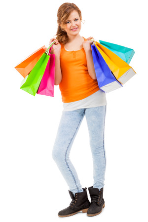 spendthrift: Happy attractive young shopaholic with her hands full of brightly coloured shopping bags from the seasonal sales standing smiling at the camera, isolated on white