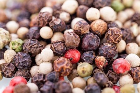 piperine: Background of whole fresh dried black peppercorns scattered on a white surface for use as a pungent spice and flavouring in cooking