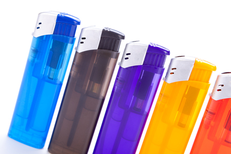 Row of vividly coloured plastic disposable lighters for smokers in red, yellow, two shades of blue and black isolated on a white background Stock Photo