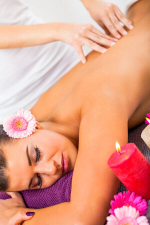 alternative practitioner: Beautiful woman having a back massage smiling in pleasure as the masseuse at the spa manipulates her shoulder muscles for complete relaxation, burning candles in the foreground
