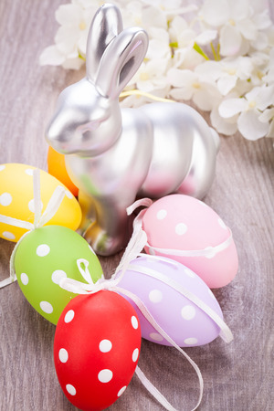 seasonal greeting: Easter still life with a metallic silver bunny ornament and eggs handpainted with colourful polka dot patterns for your seasonal greeting Stock Photo