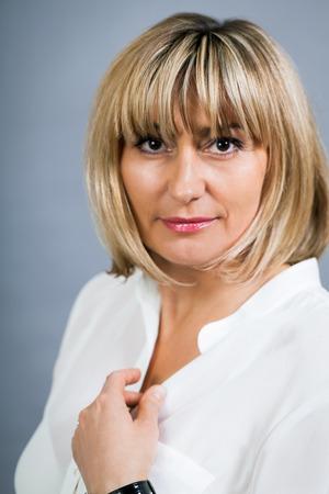 Lachende vertrouwen van middelbare leeftijd blonde vrouw in een frisse witte blouse staande met haar hand op haar heup lachend naar de camera, op grijs