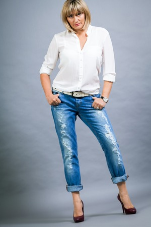 Trendy middle-aged woman with a charming smile and shoulder length blond hair in fashionable modern jeans and high heels posing with her hands in her pockets full length on grey