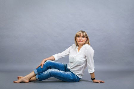 Trendy middle-aged woman with a charming smile and shoulder length blond hair in fashionable modern jeans and high heels posing with her hands in her pockets full length on grey photo