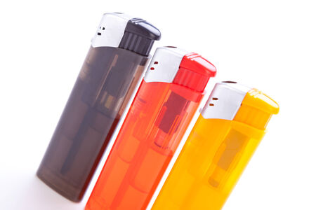 Row of vividly coloured plastic disposable lighters for smokers in red, yellow, two shades of blue and black isolated on a white background Stock Photo - 26393317