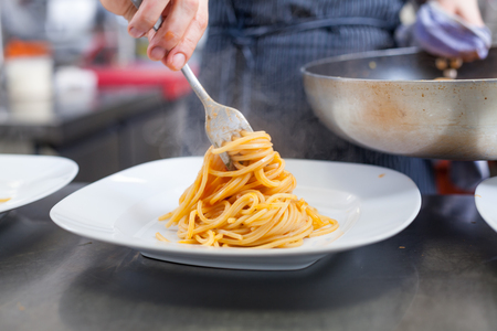 plating: Chef plating up seafood pasta placing spaghetti twirled around a fork alongside a grilled prawn on a plate in a commercial restaurant