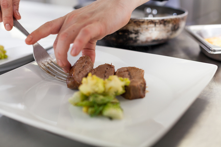 silver plated: Chef plating up food in a restaurant pouring a gravy or sauce over the meat before serving it to the customer, close up view of his hand and the gravy boat