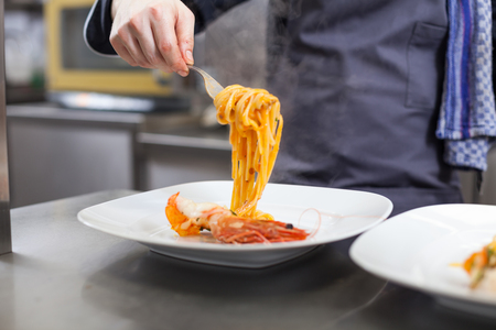 Chef plating up seafood pasta placing spaghetti twirled around a fork alongside a grilled prawn on a plate in a commercial restaurant