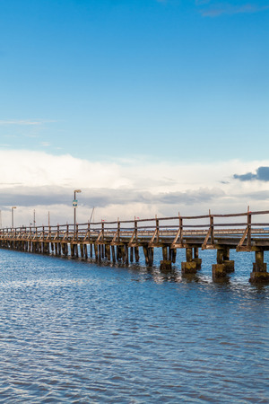 Bridge or pier stretching diagonally across an expanse of calm tranquil blue sea with a rippling surface under a cloudy blue sunny sky in a beautiful background image photo