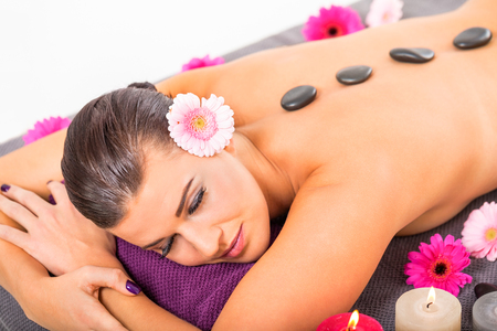 young attractive woman hot stone massage wellness  salon healthcare photo