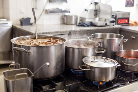 Cooking in a commercial kitchen with large stainless steel pots filled with stew and vegetables on a central gas hob photo