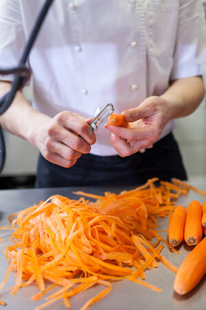 caterers: Chef in uniform preparing fresh carrot batons slicing them by hand as he stands at a kitchen counter, close up view of his hands