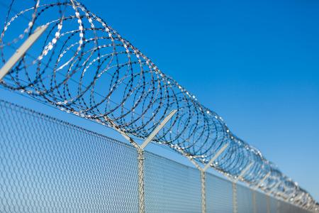 Opgerolde prikkeldraad met zijn scherpe stalen weerhaken op de top van een gaas omheining waarborgen van de veiligheid en beveiliging, het voorkomen van de toegang of het ontsnappen van gevangenen, de blauwe hemel achtergrond