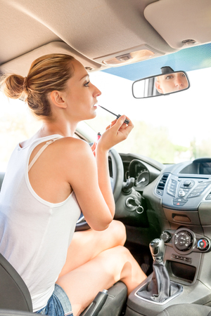 refreshes: Beautiful young woman in casual summer clothing applying makeup in the car using the rear view mirror to apply red lip gloss as she refreshes her appearance Stock Photo