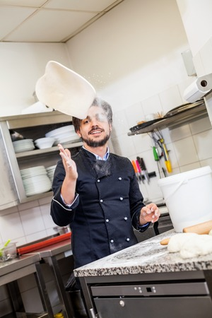 Professional cook or chef in a commercial kitchen tossing dough while making pastries for desserts in a restaurant or hotel photo