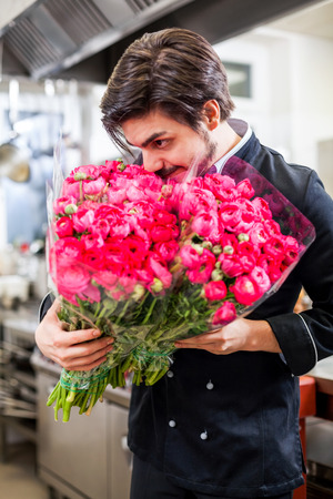 Smiling professional cook or chef holding bunches of fresh flowers for table decoration and garnish as he stands in uniform in a commercial kitchen of a restaurant or hotel photo