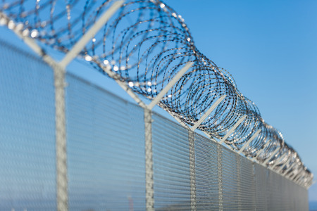 perimeter: Coiled razor wire with its sharp steel barbs on top of a wire mesh perimeter fence ensuring safety and security, preventing access or the escape of prisoners, blue sky background Stock Photo