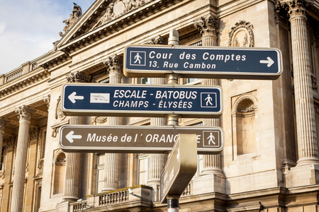 Signposts in Paris centre pointing the way to a museum, an audit court and the Champs Elysees with the steps to the Batobus which takes tourists for trips on the Seine River