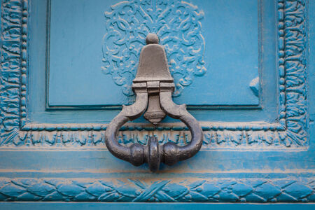 Brass door handle with a long escutcheon and lock on a colorful blue painted wooden door with a glass panel, close up view photo