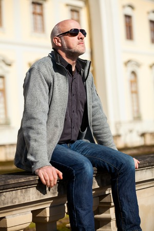 Stylish middle-aged man in sunglasses enjoying the sun sitting outdoors on a stone wall in an urban environment