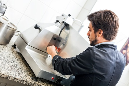 Commercial cook or chef slicing cold meat on a large rotary cutter in restaurant or hotel while preparing ingredients for the evening meal photo