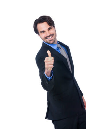 Enthusiastic handsome businessman giving a thumbs up gesture of approval and success as he looks at the camera with a beaming smile, isolated on white