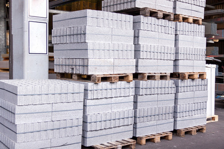 warehouse building: Cement building blocks stacked on pallets used for transportation and distribution at a hardware depot, warehouse or on a construction site Stock Photo
