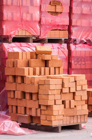 Red clay building bricks stacked on pallets still wrapped in their plastic for delivery at a warehouse, factory or construction site photo