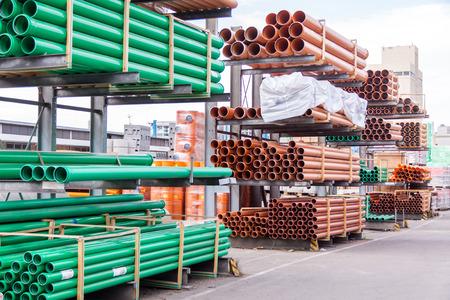 Kunststof buizen gestapeld in een fabriek of magazijn werf voor gebruik in de leidingen of riolering installaties op een bouwplaats Stockfoto