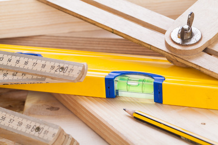 Close up view of a colorful yellow carpenters level, ruler and right angle lying on planks of new hardwood together with a pencil for measurements in a carpentry, construction, DIY and joinery concept Фото со стока