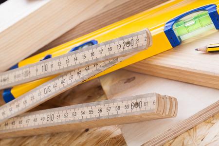 joinery: Primo piano vista di un colorato livello falegnami gialle, righello e ad angolo retto disteso su tavole di legno nuovo insieme con una matita per le misurazioni in un concetto di carpenteria, edilizia, bricolage e falegnameria