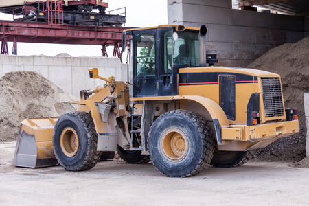 front end loader: Front end loader with its bucket or scoop down parked in front of a warehouse on paving