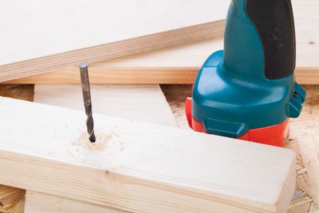 joinery: Funzionamento a batteria trapano a mano in piedi tra tavole di legno nuovo, con un po 'd'acciaio a sinistra sporge da un bordo in un concetto di fai da te, carpenteria o falegnameria