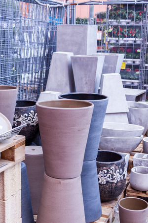 Glazed and unglazed ceramic flower pots in a variety of sizes and colors stacked on wooden pallets outside a pottery, warehouse or commercial store photo