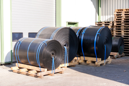 roofing membrane: Rolls of black industrial plastic tied to wooden pallets outside a warehouse or factory for use as waterproofing in building and construction