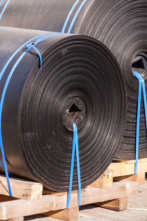 Rolls of black industrial plastic tied to wooden pallets outside a warehouse or factory for use as waterproofing in building and construction photo