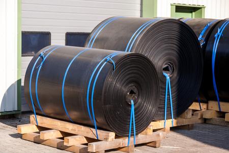 Rollen van zwarte industriële plastic vastgebonden aan houten pallets buiten een magazijn of de fabriek voor gebruik als waterdicht in de bouw
