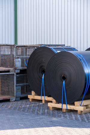 waterproofing material: Rolls of black industrial plastic tied to wooden pallets outside a warehouse or factory for use as waterproofing in building and construction