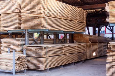 Houten panelen opgeslagen in een industriële loods op metalen stellingen voor gebruik in de bouw en de bouw, niemand in zicht