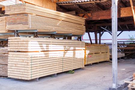 Houten panelen opgeslagen in een industriële loods op metalen stellingen voor gebruik in de bouw en de bouw, niemand gezien